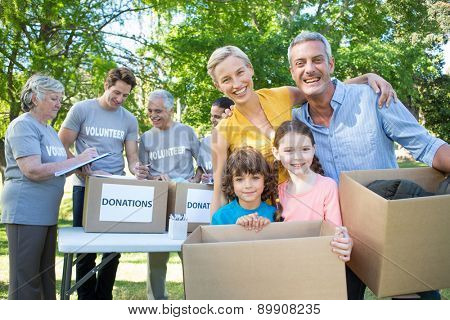 Happy family holding boxes and smiling at the camera on a sunny day