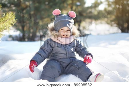 Funny Child Playing On The Snow In Warm Sunny Winter Day