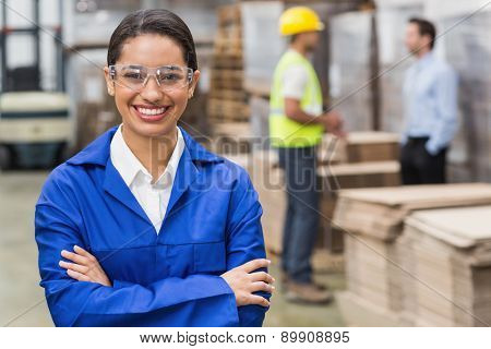 Manager wearing protective mask looking at camera in a large warehouse