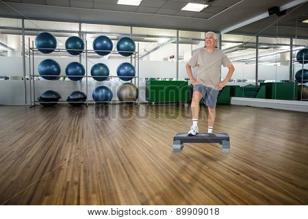 Full length portrait of a senior man against large empty fitness studio with shelf of exercise balls