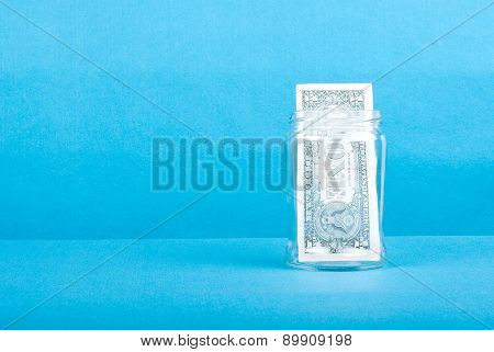 One Dollar In A Glass Jar On The Right Side, Side View, Place For Text