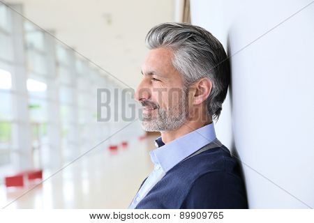 Portrait of smiling mature man standing in corridor
