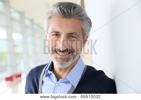 Portrait of smiling mature man standing in corridor