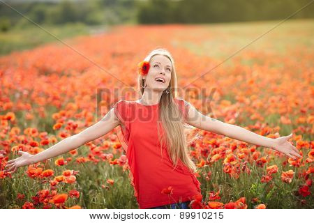 Happy woman on poppy flower field