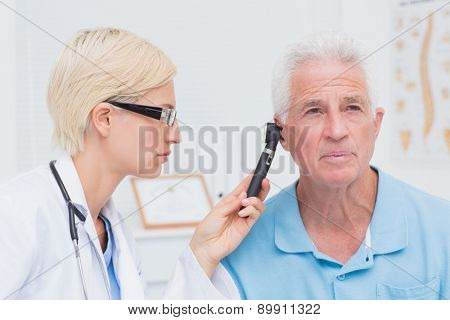 Female doctor examining male patients ear with otoscope in clinic
