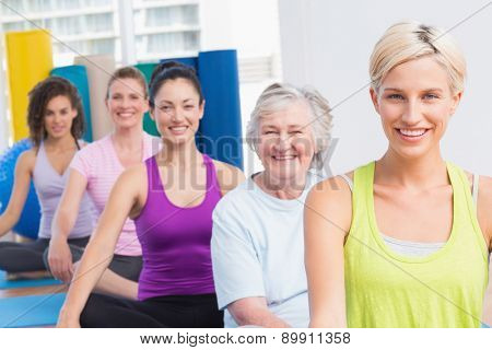 Portrait of happy fit women practicing yoga during fitness class