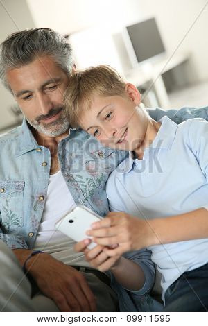 Daddy with son playing with smartphone
