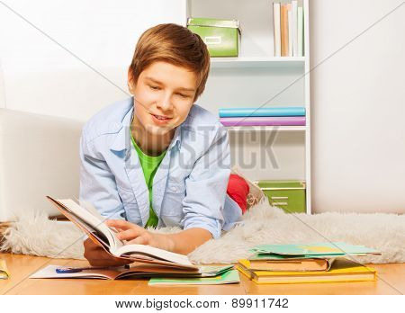 Smart boy with book and textbook lay on the floor