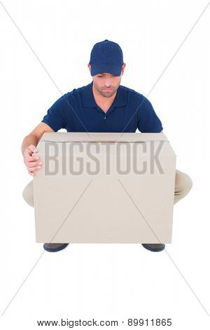 Full length of delivery man crouching while picking cardboard box on white background