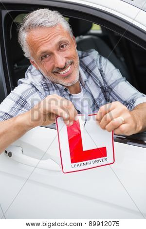 Driver smiling and tearing l plate in his car