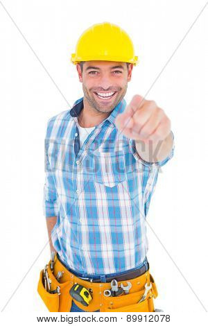 Portrait of smiling handyman pointing at you on white background