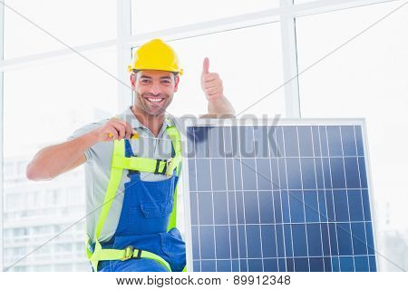 Portrait of smiling male worker tightening solar panel while gesturing thumbs up in bright office