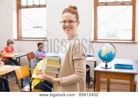 Teacher smiling at camera while holding stack of notebooks at the elementary school