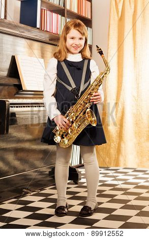 Girl in school uniform dress holds alto saxophone