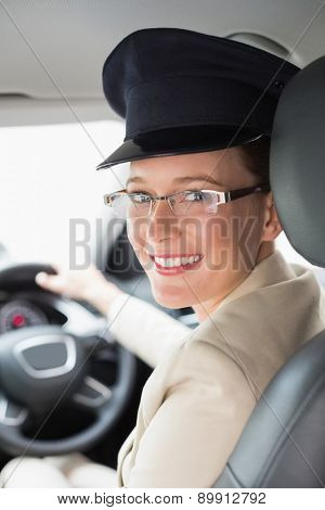 Chauffeur smiling at camera in the car