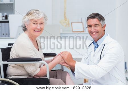 Portrait of happy doctor holding senior patients hands in clinic