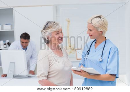 Nurse discussing with female patient while doctor using computer in background at clinic