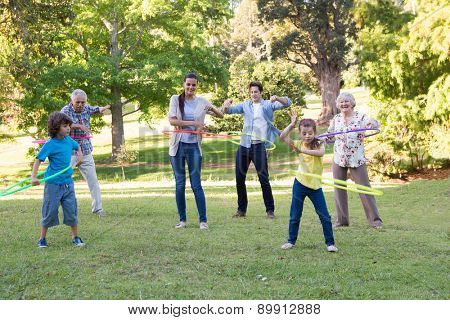 Extended family playing with hula hoops on a sunny day