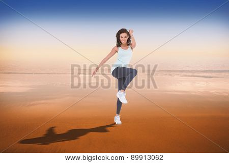 Fit woman doing aerobic exercise against hazy blue sky