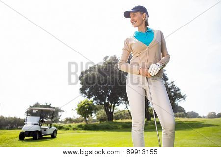 Female golfer smiling and posing on a sunny day at the golf course