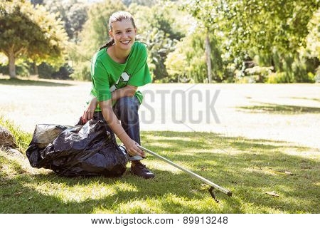 Environmental activist picking up trash on a sunny day
