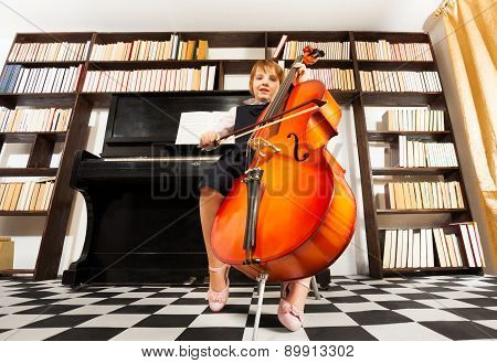 One small girl in uniform dress playing on cello