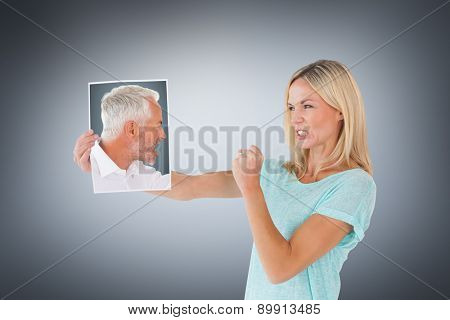 Angry man shouting at piece of paper against grey vignette