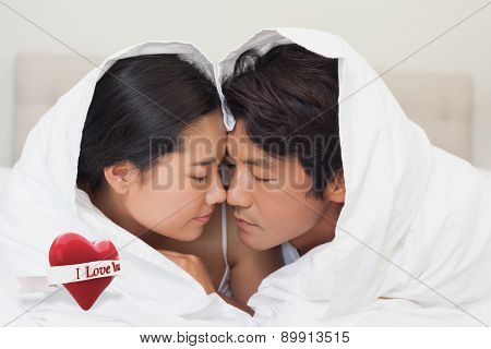 Happy couple lying on bed together under the duvet against heart with scroll