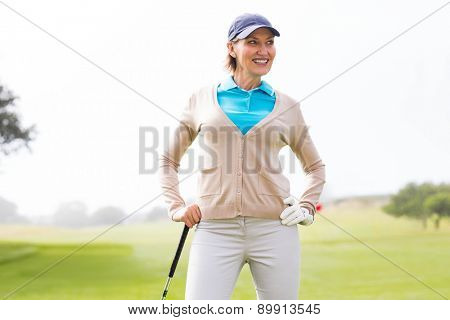 Female golfer standing with hand on hip on a sunny day at the golf course