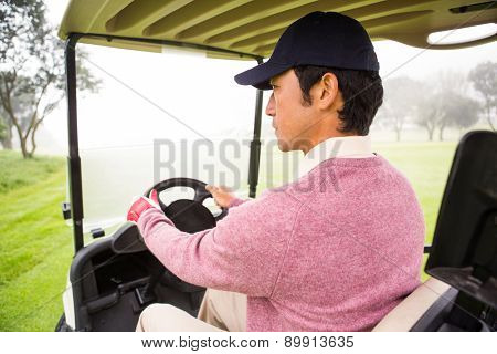 Golfer driving his golf buggy at the golf course