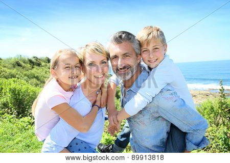 Parents giving piggyback ride to kids by the sea