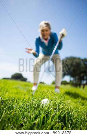 Worried female golfer looking at golf ball on a sunny day at the golf course
