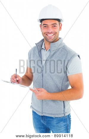Portrait of smiling supervisor writing on clipboard on white background
