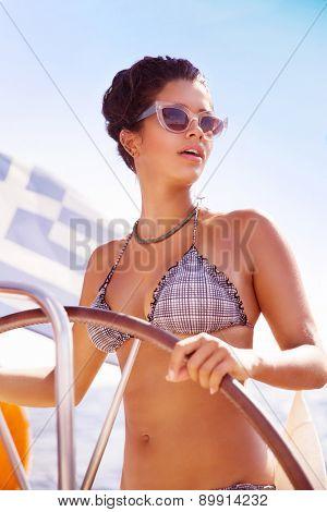 Portrait of beautiful sexy woman driving sailboat, active lifestyle, fashion look, enjoying luxury sea cruise, having fun in summer adventure