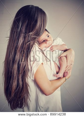 Gentle mother with little baby isolated on gray background, woman with dark long hair holding her precious newborn daughter, love and happy motherhood concept