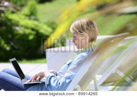 Woman using laptop relaxing in long chair