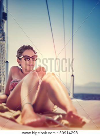 Sexy woman on sailboat lying down on the deck of luxury sailboat, tanning on bright sun light, enjoying sea cruise, active summer holidays and vacation