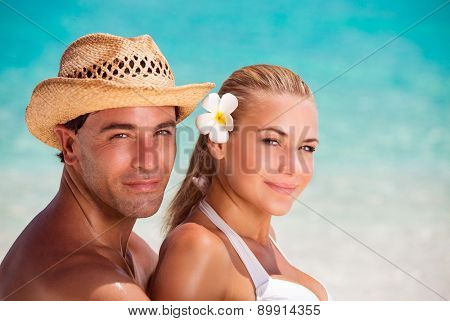 Closeup portrait of beautiful young lovers on the beach, handsome guy wearing straw hat hugging his nice girlfriend with flower in hair, romantic summer vacation