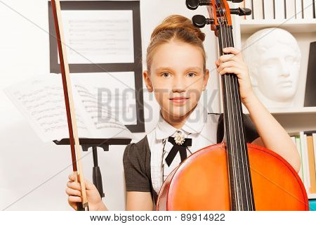 Portrait of girl holding fiddle-bow to play cello