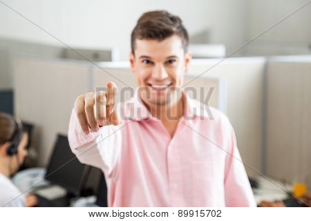 Portrait of smiling male call center employee pointing at you in office