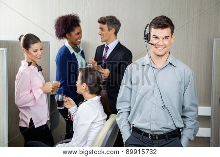 Confident male customer service representative wearing headphones while manager discussing with team in background at call center