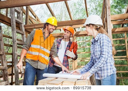 Happy male and female workers discussing over blueprint in incomplete wooden cabin at site
