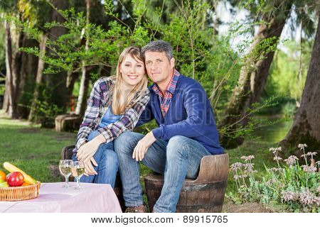 Portrait of happy couple sitting on chairs at campsite