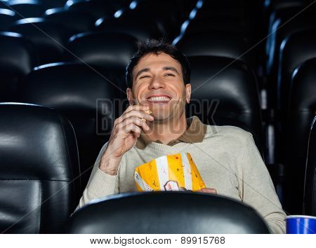 Happy man eating popcorn while watching movie in cinema theater