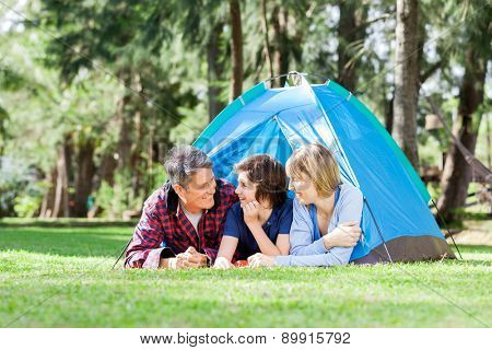Happy family relaxing inside tent on camping holiday