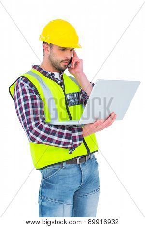 Handyman on the phone holding laptop on white backboard