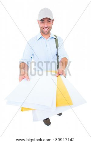 Portrait of happy postman delivering lettes on white background