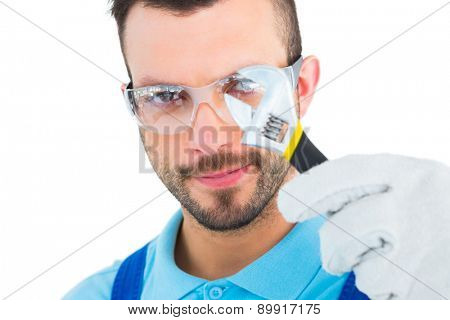 Repairman looking through adjustable wrench on white background