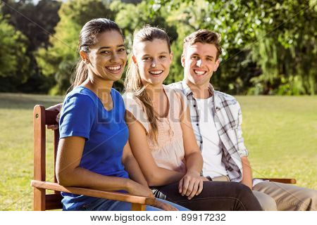 Happy friends sitting on bench on a sunny day