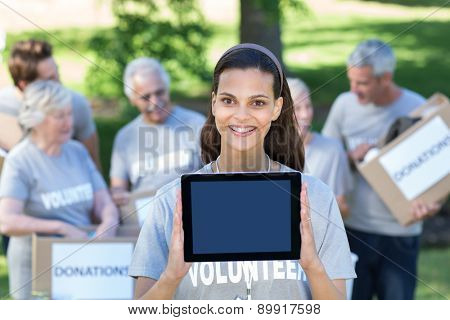 Smiling volunteer brunette showing tablet pc screen on a sunny day